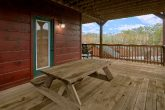 Cabin with picnic table and hot tub on deck
